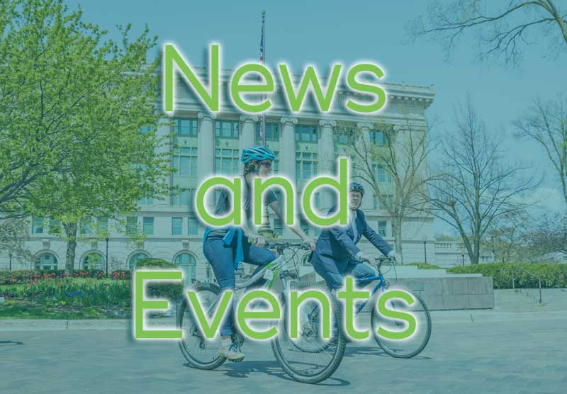 """News and Events"" over image of Mayor Larson and another person cycling in the Duluth Civic Center"