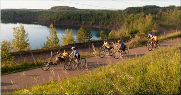 Cyclists riding next to a lake on paved bike trail